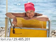 Купить «Женщина в красной бандане с солнечными очками в руках лежит на желтом лежаке на пляже», фото № 29485201, снято 23 июля 2018 г. (c) Кекяляйнен Андрей / Фотобанк Лори