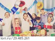 Купить «Boys and girls handing gifts to each other during dinner», фото № 29485261, снято 26 июня 2019 г. (c) Яков Филимонов / Фотобанк Лори