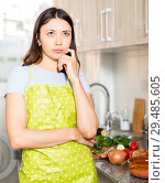 Купить «Young girl housewife in apron looking tired at kitchen», фото № 29485605, снято 18 апреля 2018 г. (c) Яков Филимонов / Фотобанк Лори
