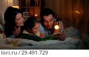 Купить «happy family reading book in bed at night at home», видеоролик № 29491729, снято 23 апреля 2019 г. (c) Syda Productions / Фотобанк Лори