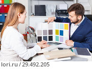 Купить «Competent seller in showroom helping young female client to choose furniture materials for her apartment», фото № 29492205, снято 9 апреля 2018 г. (c) Яков Филимонов / Фотобанк Лори