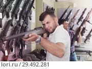 Купить «Friends choosing air-powered gun», фото № 29492281, снято 4 июля 2017 г. (c) Яков Филимонов / Фотобанк Лори