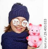 Купить «Веселая девочка в очках с надписью 2019 держит гипсового поросенка -копилку», фото № 29493033, снято 21 ноября 2018 г. (c) Элина Гаревская / Фотобанк Лори