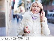 Купить «Female in the city in scarf and jacket talking on phone», фото № 29496453, снято 21 декабря 2017 г. (c) Яков Филимонов / Фотобанк Лори
