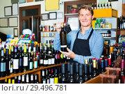 Купить «Man seller wearing apron having bottle of wine in hands», фото № 29496781, снято 6 июня 2020 г. (c) Яков Филимонов / Фотобанк Лори