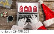 Купить «Video composition with snow over desk  with santa hand on laptop», видеоролик № 29498205, снято 14 декабря 2018 г. (c) Wavebreak Media / Фотобанк Лори