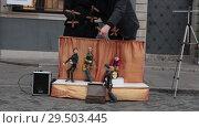 Купить «Performance. Puppets plays instruments on the little stage. Two men control the marionettes», видеоролик № 29503445, снято 6 декабря 2019 г. (c) Константин Шишкин / Фотобанк Лори