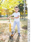 Купить «Boy on orange scooter», фото № 29503837, снято 25 сентября 2015 г. (c) Сергей Сухоруков / Фотобанк Лори