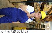 Купить «Portrait of young woman worker in uniform speak by mobile in build store», видеоролик № 29508405, снято 16 октября 2018 г. (c) Яков Филимонов / Фотобанк Лори