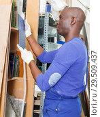 Купить «African-American workman looking at glass samples», фото № 29509437, снято 16 мая 2018 г. (c) Яков Филимонов / Фотобанк Лори