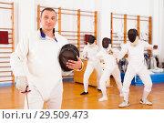 Купить «Young man fencer in uniform and mask standing with foil», фото № 29509473, снято 11 июля 2018 г. (c) Яков Филимонов / Фотобанк Лори