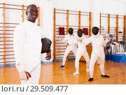 Купить «African american male fencer in uniform standing with mask and foil», фото № 29509477, снято 11 июля 2018 г. (c) Яков Филимонов / Фотобанк Лори