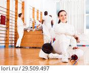 Купить «Woman in uniform sitting on floor at fencing training», фото № 29509497, снято 11 июля 2018 г. (c) Яков Филимонов / Фотобанк Лори