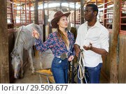 Купить «Girl and man having emotional discussion at stable», фото № 29509677, снято 2 октября 2018 г. (c) Яков Филимонов / Фотобанк Лори