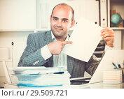 Купить «Businessman in shirt viewing documents at the table», фото № 29509721, снято 3 мая 2017 г. (c) Яков Филимонов / Фотобанк Лори