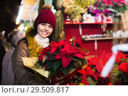 Купить «Girl buying floral compositions at Christmas market», фото № 29509817, снято 12 декабря 2016 г. (c) Яков Филимонов / Фотобанк Лори