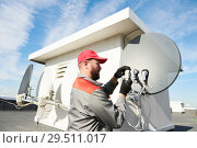 Купить «Service worker installing and fitting satellite antenna dish for cable TV», фото № 29511017, снято 15 октября 2018 г. (c) Дмитрий Калиновский / Фотобанк Лори