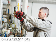 Купить «heating engineer or plumber in boiler room installing or adjusting manometer», фото № 29511045, снято 5 октября 2018 г. (c) Дмитрий Калиновский / Фотобанк Лори