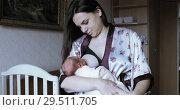 Beautiful woman is feeding the baby. Стоковое видео, видеограф Потийко Сергей / Фотобанк Лори