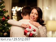 Купить «happy couple with christmas gift hugging at home», фото № 29512097, снято 11 января 2018 г. (c) Syda Productions / Фотобанк Лори