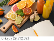 Купить «close up of fruits, juices and notebook on table», фото № 29512393, снято 4 апреля 2018 г. (c) Syda Productions / Фотобанк Лори
