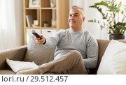 Купить «man with remote control watching tv at home», фото № 29512457, снято 14 апреля 2018 г. (c) Syda Productions / Фотобанк Лори