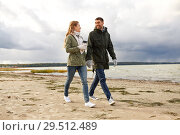 Купить «couple with tumbler walking along autumn beach», фото № 29512489, снято 29 сентября 2018 г. (c) Syda Productions / Фотобанк Лори