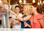 Купить «happy women pouring wine from dispenser at bar», фото № 29512721, снято 25 июня 2018 г. (c) Syda Productions / Фотобанк Лори