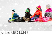happy little kids sliding on sleds in winter. Стоковое фото, фотограф Syda Productions / Фотобанк Лори