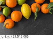 Купить «close up of citrus fruits on stone table», фото № 29513085, снято 4 апреля 2018 г. (c) Syda Productions / Фотобанк Лори