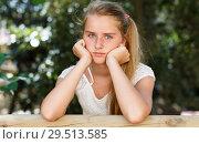 Купить «Upset teenage girl standing near fence in green park at summer day», фото № 29513585, снято 20 июля 2018 г. (c) Яков Филимонов / Фотобанк Лори