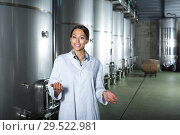 Купить «Female in uniform standing in winery compartment», фото № 29522981, снято 17 января 2019 г. (c) Яков Филимонов / Фотобанк Лори