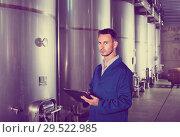 Купить «Young man in coat taking notes on wine factory», фото № 29522985, снято 19 января 2019 г. (c) Яков Филимонов / Фотобанк Лори