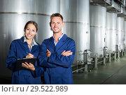 Купить «Two young winery professional standing in protective uniform», фото № 29522989, снято 19 января 2019 г. (c) Яков Филимонов / Фотобанк Лори