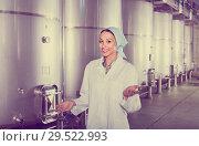 Купить «Portrait of woman standing on wine factory in secondary fermentation section», фото № 29522993, снято 13 декабря 2019 г. (c) Яков Филимонов / Фотобанк Лори