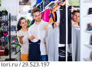 Couple examining various sports clothes in sports store. Стоковое фото, фотограф Яков Филимонов / Фотобанк Лори