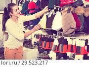 Купить «girl deciding on warm hat in sports store», фото № 29523217, снято 22 ноября 2016 г. (c) Яков Филимонов / Фотобанк Лори