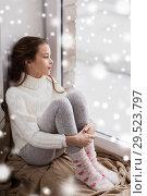 Купить «sad girl sitting on sill at home window in winter», фото № 29523797, снято 5 ноября 2016 г. (c) Syda Productions / Фотобанк Лори