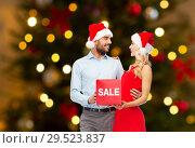 Купить «couple in santa hats with sale sign on christmas», фото № 29523837, снято 3 октября 2015 г. (c) Syda Productions / Фотобанк Лори