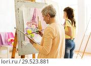Купить «senior woman painting at art school studio», фото № 29523881, снято 26 мая 2017 г. (c) Syda Productions / Фотобанк Лори