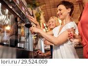 Купить «happy women pouring wine from dispenser at bar», фото № 29524009, снято 25 июня 2018 г. (c) Syda Productions / Фотобанк Лори