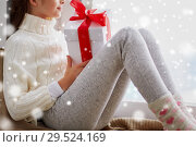 Купить «girl with christmas gift sitting on sill at home», фото № 29524169, снято 5 ноября 2016 г. (c) Syda Productions / Фотобанк Лори