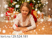 Купить «smiling girl writing christmas wish list at home», фото № 29524181, снято 22 декабря 2017 г. (c) Syda Productions / Фотобанк Лори