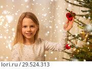 Купить «happy girl in red dress decorating christmas tree», фото № 29524313, снято 22 декабря 2017 г. (c) Syda Productions / Фотобанк Лори