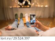 Купить «close up of couple taking foot photo by smartphone», фото № 29524397, снято 13 января 2018 г. (c) Syda Productions / Фотобанк Лори