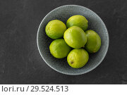Купить «close up of whole limes in bowl on slate table top», фото № 29524513, снято 4 апреля 2018 г. (c) Syda Productions / Фотобанк Лори