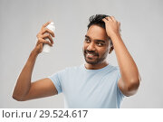 Купить «smiling indian man applying hair spray over gray», фото № 29524617, снято 27 октября 2018 г. (c) Syda Productions / Фотобанк Лори