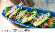Купить «Delicious salmon tartare garnish with avocado on blue plate», фото № 29530489, снято 21 сентября 2019 г. (c) Яков Филимонов / Фотобанк Лори