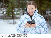 Купить «Довольная женщина со смартфоном в руках в зимнем лесу», фото № 29536453, снято 2 января 2015 г. (c) Кекяляйнен Андрей / Фотобанк Лори
