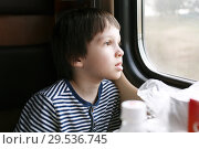 Lovely little boy looks out of window in the train. Стоковое фото, фотограф ivolodina / Фотобанк Лори